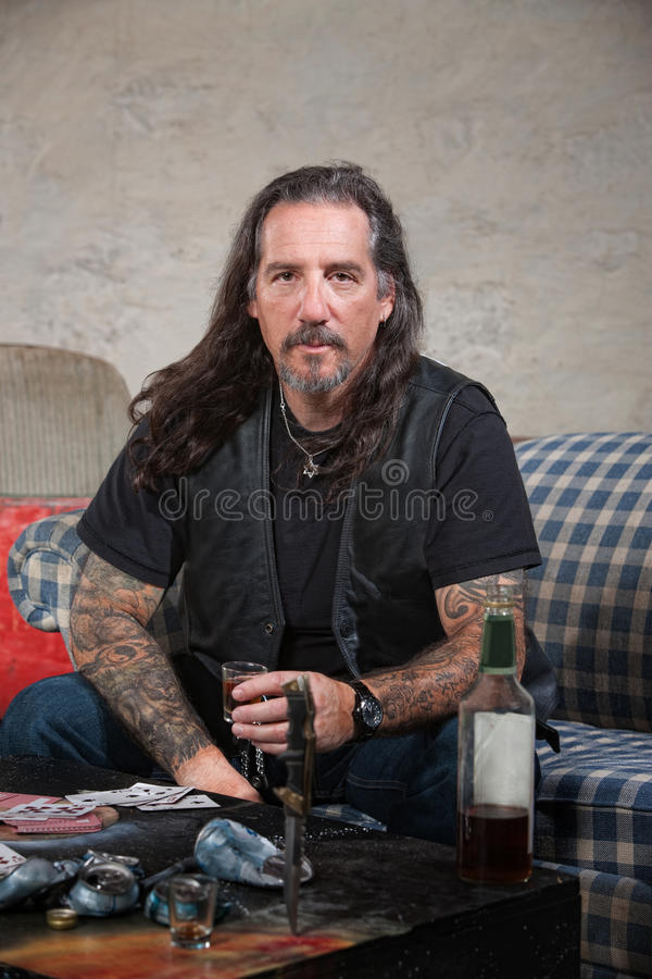 Biker Gang Member with Weapons and Alcohol. Serious biker gang member with liquor and dagger on table royalty free stock images