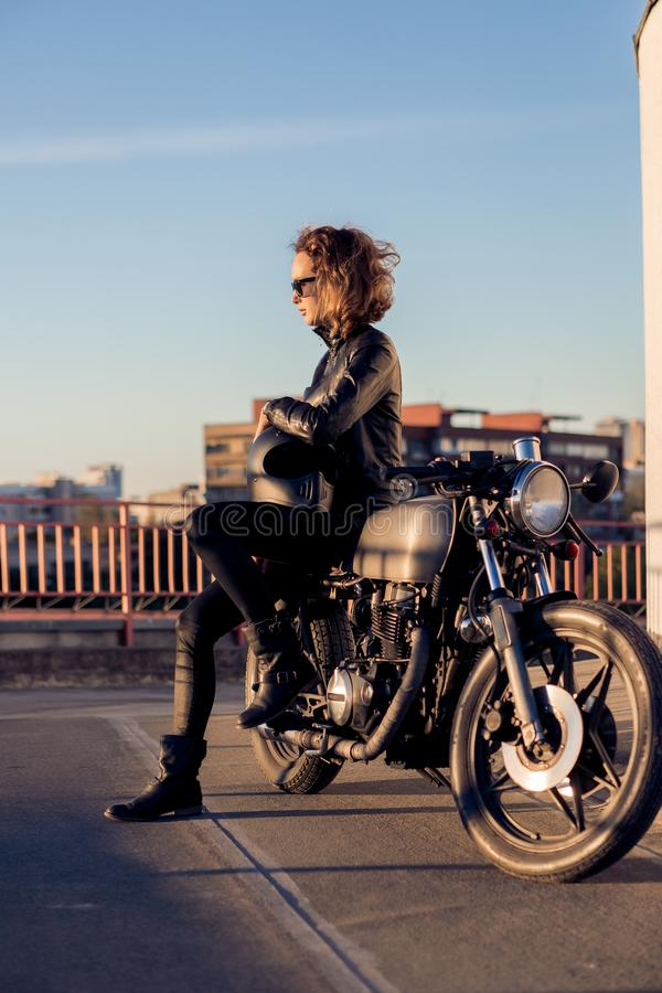 Biker girl on caferacer motorcycle. Biker beautiful woman in black trendy leather jacket sit on vintage custom made caferacer motorcycle. Urban roof parking royalty free stock photo