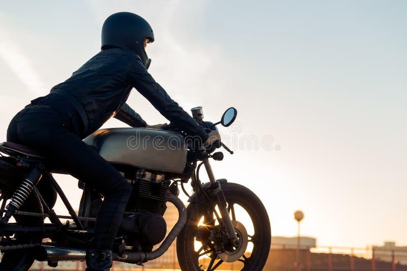 Biker girl on caferacer motorcycle. Biker female in black leather jacket and full face helmet sit on vintage custom caferacer motorcycle. Urban roof parking stock images