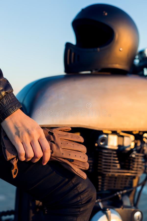Biker girl on caferacer motorcycle. Biker woman sit on vintage custom caferacer motorcycle. Black full face helmet and leather gloves. Urban roof parking stock photos