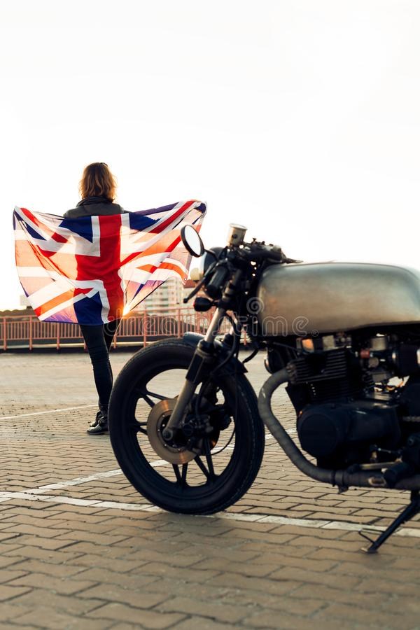 Biker girl on caferacer motorcycle. Biker woman on vintage custom caferacer motorcycle. Girl in black leather jacket with Britain flag. Urban roof parking royalty free stock photos