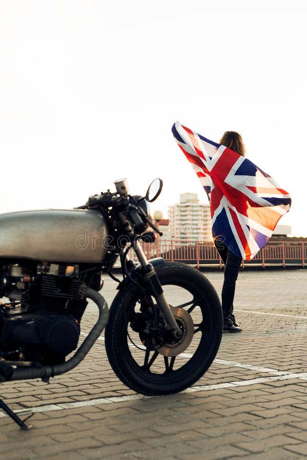 Biker girl on caferacer motorcycle. Biker woman on vintage custom caferacer motorcycle. Girl in black leather jacket with UK flag. Urban roof parking, sunset in royalty free stock photos