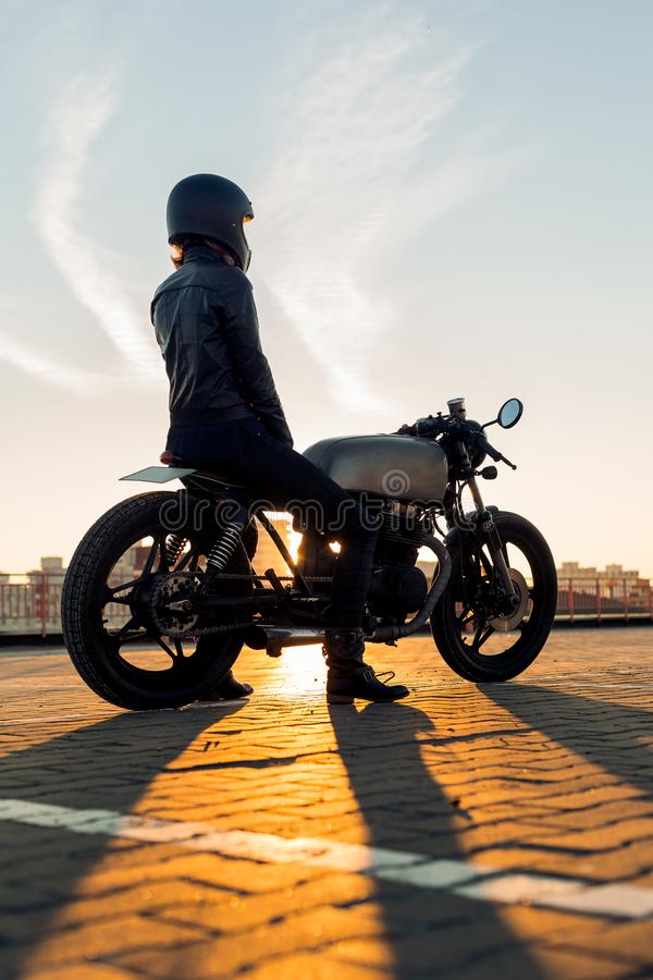 Biker girl on caferacer motorcycle. Biker female in black leather jacket and full face helmet sit on vintage custom caferacer motorbike. Urban roof parking royalty free stock photos
