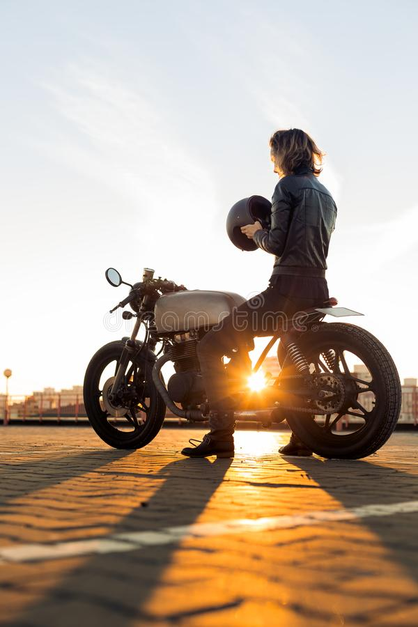 Biker girl on caferacer motorcycle. Biker lady in black leather jacket and full face helmet sit on vintage custom caferacer motorbike. Urban roof parking royalty free stock photos