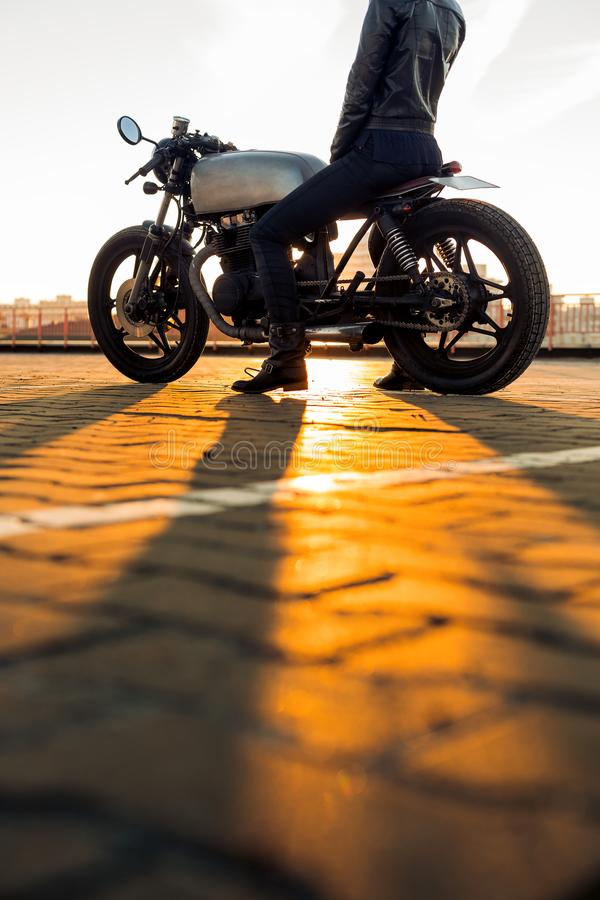 Biker girl on caferacer motorcycle. Biker lady in black leather jacket and full face helmet sit on vintage custom caferacer motorcycle. Urban roof parking royalty free stock image