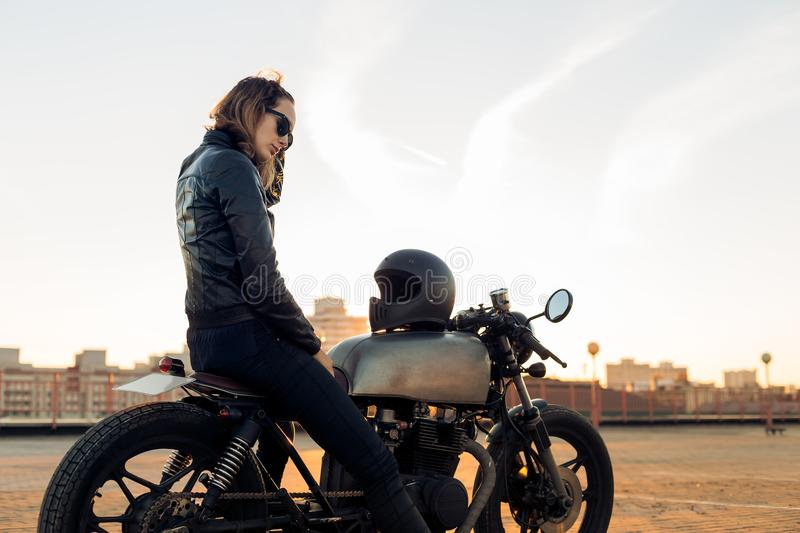 Biker girl on caferacer motorcycle. Biker lady in black leather jacket sit on vintage custom caferacer motorbike and touch her hair. Urban roof parking, sunset stock photos