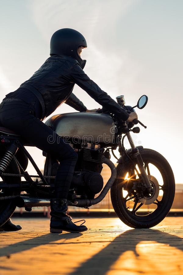 Biker girl on caferacer motorcycle. Biker woman in black leather jacket and full face helmet sit on vintage custom caferacer motorbike. Urban roof parking royalty free stock photography