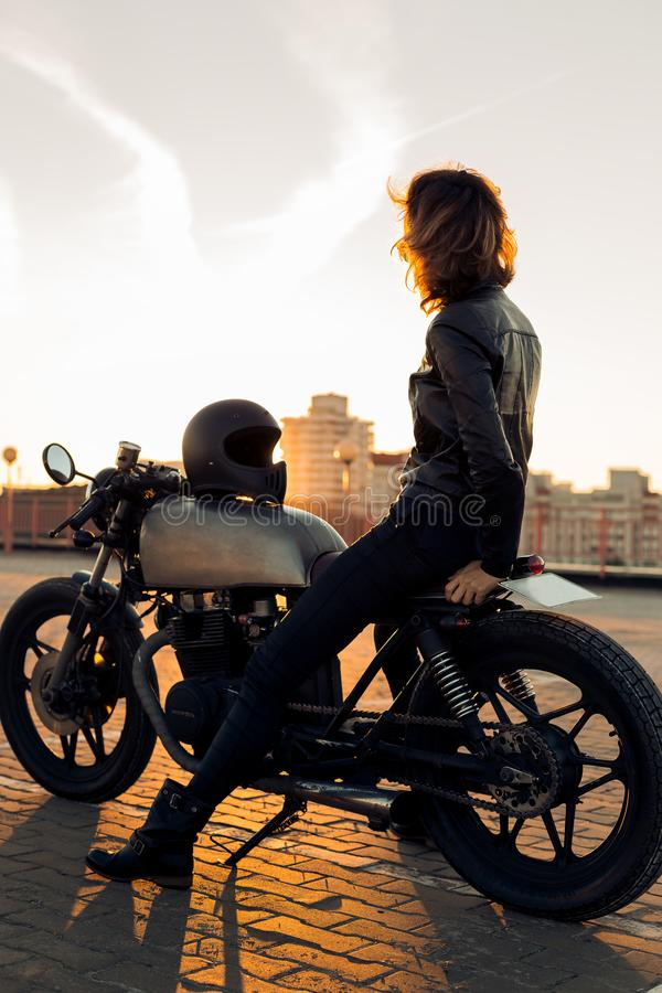 Biker girl on caferacer motorcycle. Biker woman in black leather jacket sit on vintage custom caferacer motorbike and touch sunglasses. Urban roof parking stock images