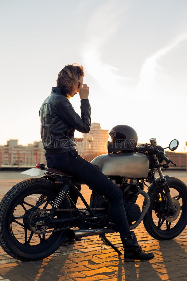 Biker girl on caferacer motorcycle. Biker woman in black leather jacket sit on vintage custom caferacer motorbike and touch sunglasses. Urban roof parking royalty free stock image