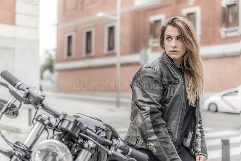 Biker girl in a leather jacket on a motorcycle stock images