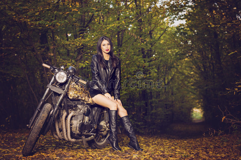 Biker girl in a leather jacket on a motorcycle stock photos