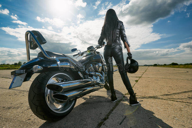 Biker girl standing by a motorcycle. Biker girl in leather jacket standing by a motorcycle. Rear view royalty free stock photography
