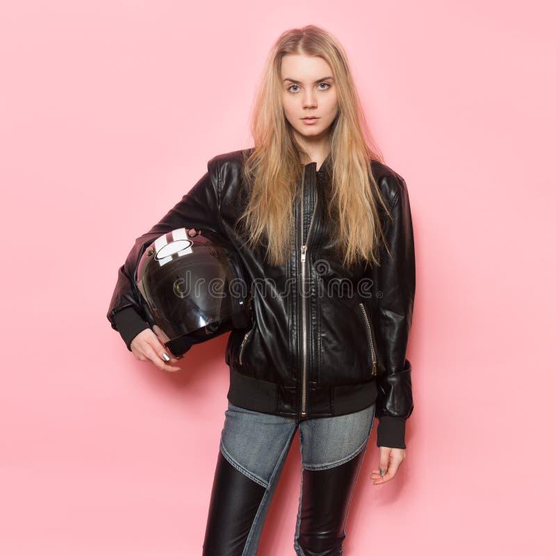 Biker girl wearing black leather jacket holding motorcycle helmet royalty free stock image
