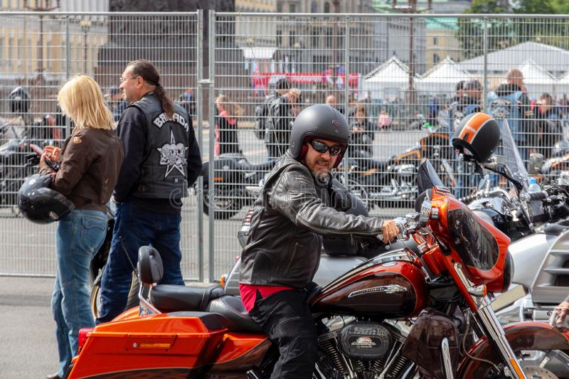 a biker in a helmet, black glasses and a brown leather jacket is sitting on a motorcycle royalty free stock image