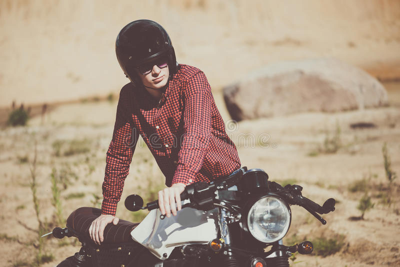 Biker with helmet start a vintage custom motorcycle. Outdoor lifestyle toned portrait. Dressed in a red shirt stock photography