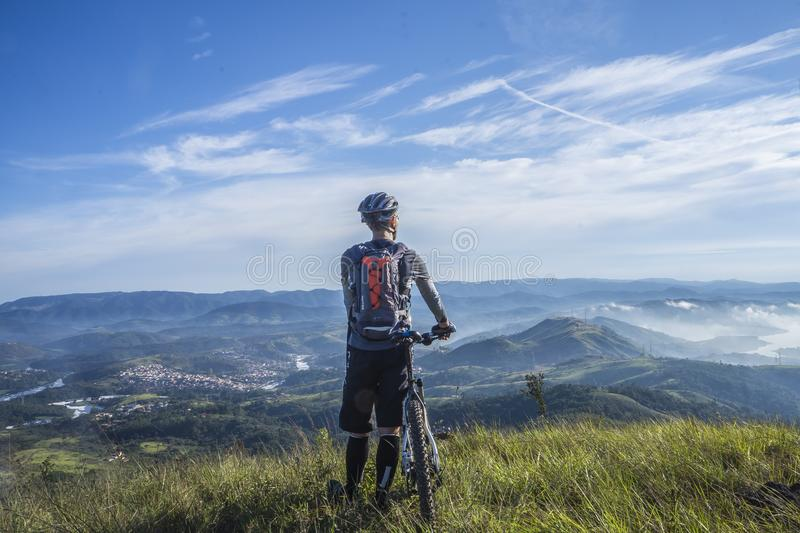 Biker Holding Mountain Bike on Top of Mountain With Green Grass stock photo