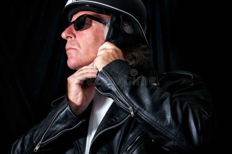 Biker in leather jacket and sunglasses adjusting helmet royalty free stock images