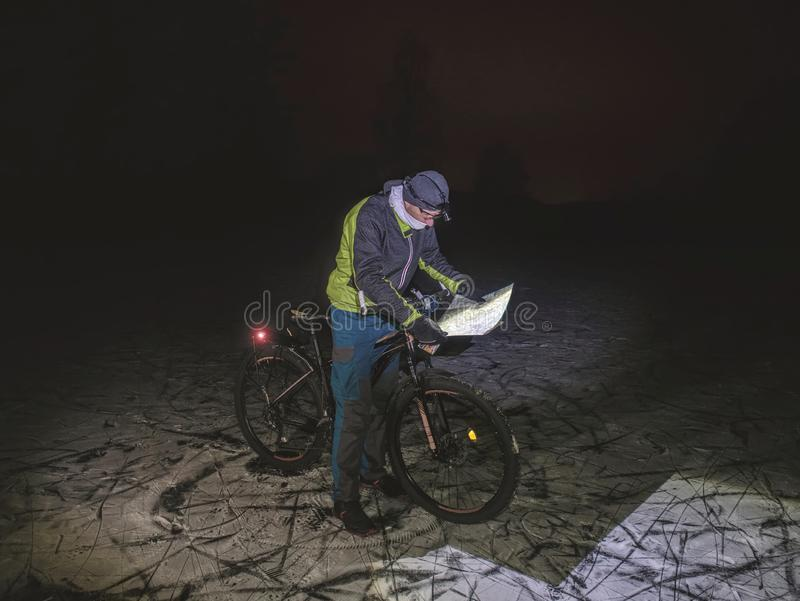Biker lost path in night snowdrift. Man with mtb. Biker lost path in night snowdrift. Man with mountain bike stay in powder snow and check map stock image