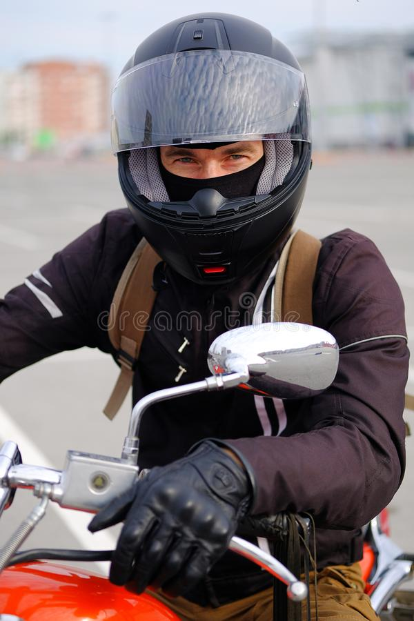 Biker man or a boy-racer in the helmet sitting on the motorcycle in classic style, looking at camera, on the free Parking at the stock images