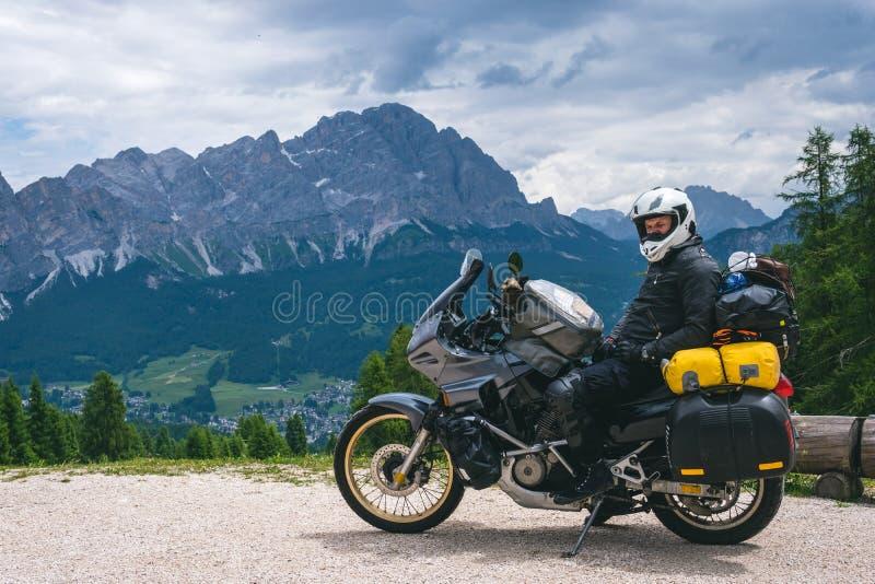 Biker man está sentado em uma moto de aventura em turnê descansa depois de uma longa viagem de estrada, montanhas de cima em segu imagens de stock royalty free