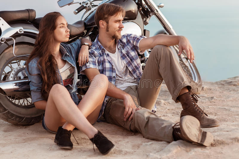 Biker man and girl sits royalty free stock photo