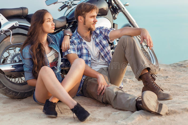 Biker man and girl sits stock photo