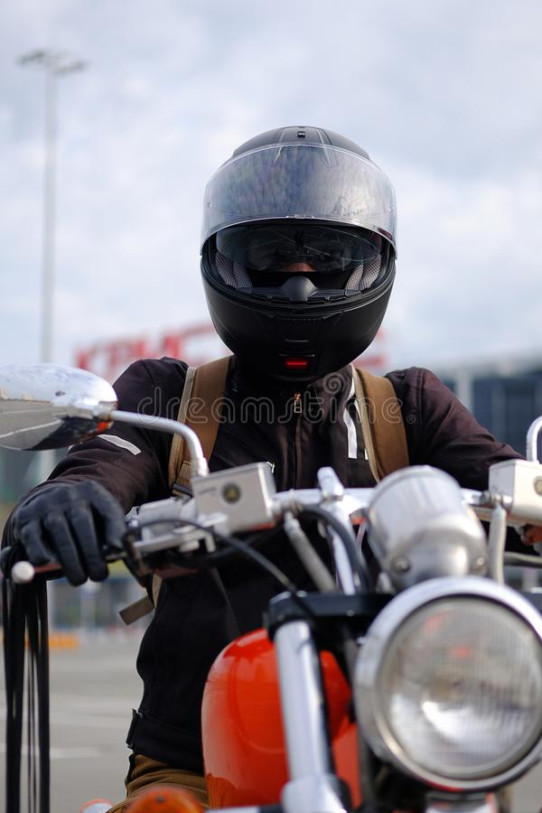 Biker man or guy-racer in a protective helmet and glasses sitting on a motorcycle classic style, looking at the camera in the stock image