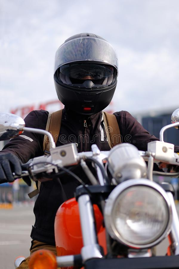 Biker man or guy-racer in a protective helmet and glasses sitting on a motorcycle classic style, looking at the camera in the royalty free stock photo