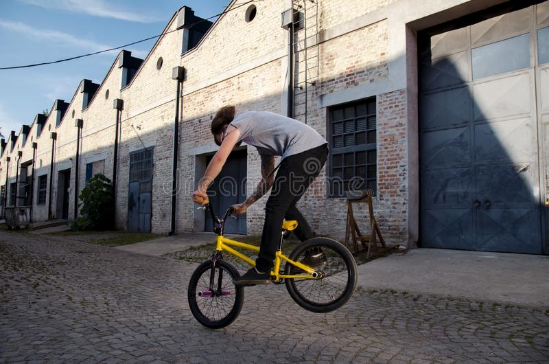 Biker man jumping with bmx bike on the street. In motion stock photo