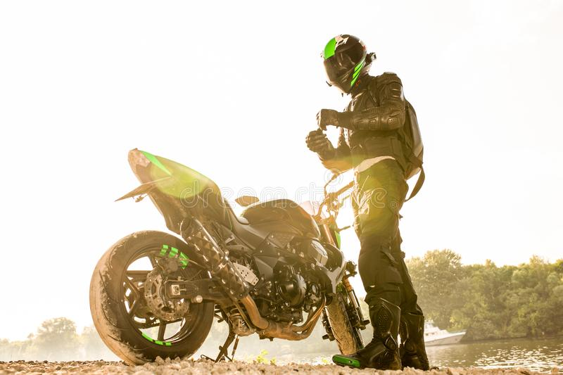Biker man and motorcycle with river background, Rider moto trip on the street at the riverside, enjoying freedom and. Active lifestyle. enduro travel touring royalty free stock photo