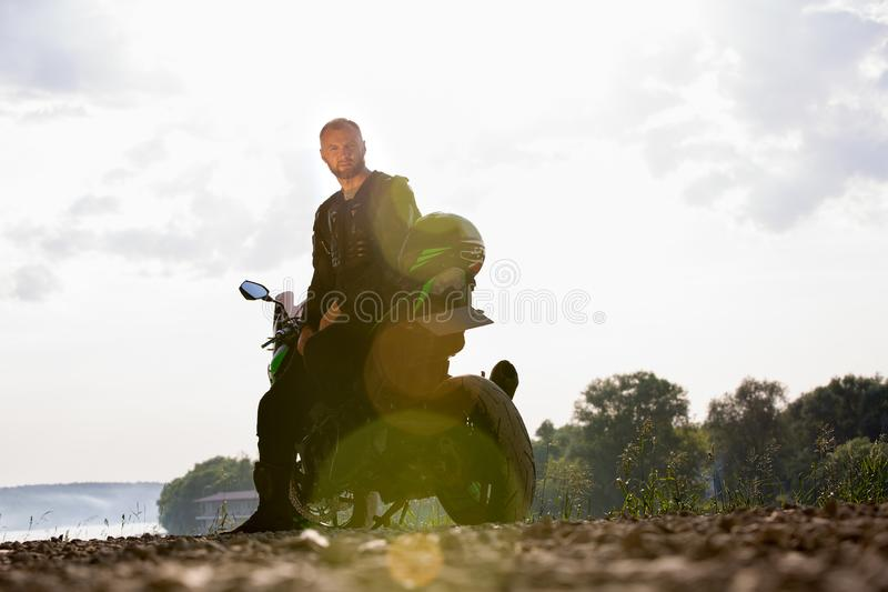 Biker man and motorcycle with river background, Rider moto trip on the street at the riverside, enjoying freedom and. Active lifestyle. enduro travel touring stock photos