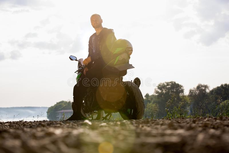 Biker man and motorcycle with river background, Rider moto trip on the street at the riverside, enjoying freedom and. Active lifestyle. enduro travel touring royalty free stock photos
