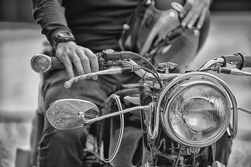 Biker man sitting on his motorcycle. Black and white style royalty free stock photo