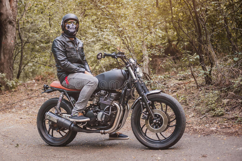 Biker man sitting on his motorcycle. Biker man wearing a leather jacket and sunglasses sitting on his motorcycle looking at camera stock photo