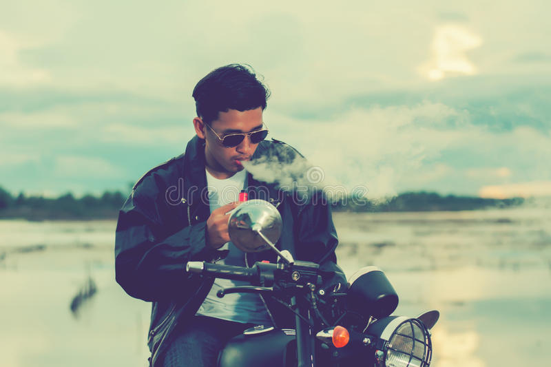 Biker man standing smokes with his motorbike beside the natural lake and beautiful, enjoying freedom and active lifestyle, having. Fun on a bikers tour.Night royalty free stock image