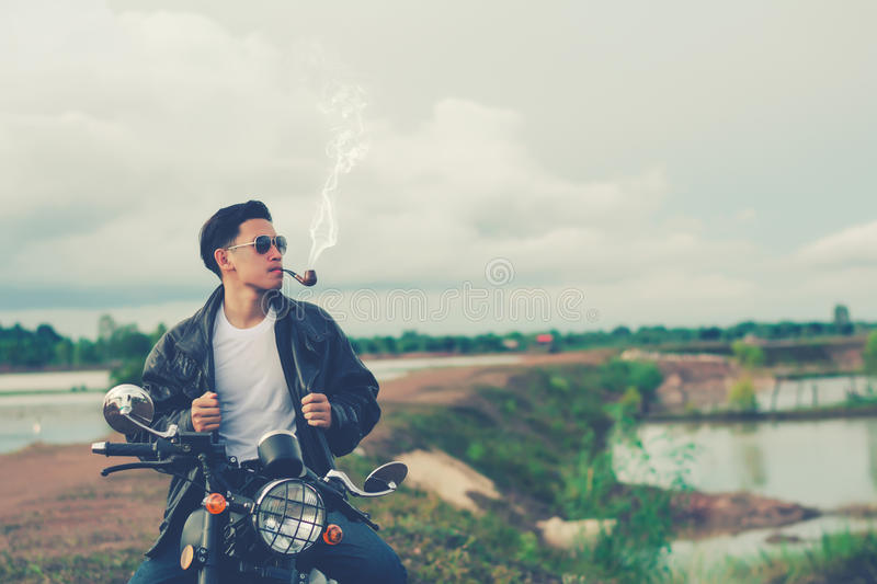 Biker man standing smokes with his motorbike beside the natural lake and beautiful, enjoying freedom and active lifestyle, having. Fun on a bikers tour.Night stock photo