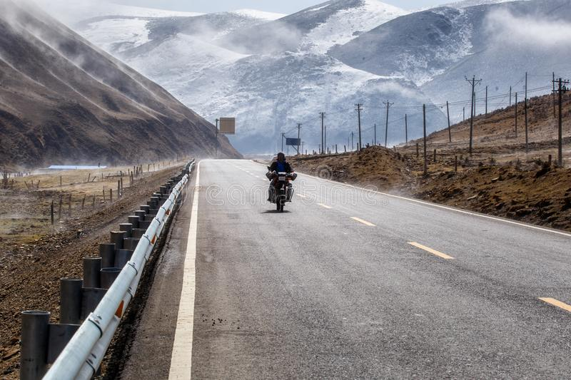 Biker motorcycle on the road beautiful winter in Tibet under snow mountain. Sichuan, China stock images