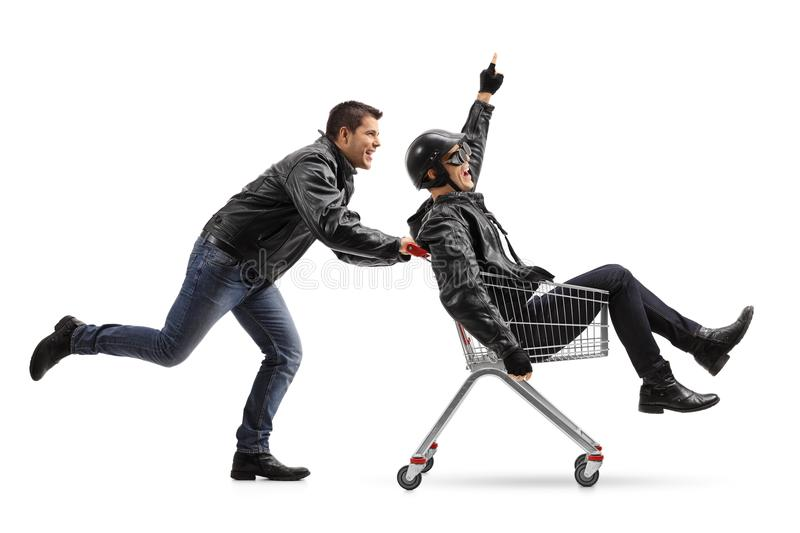 Biker pushing a shopping cart with another biker holding his fin stock photography
