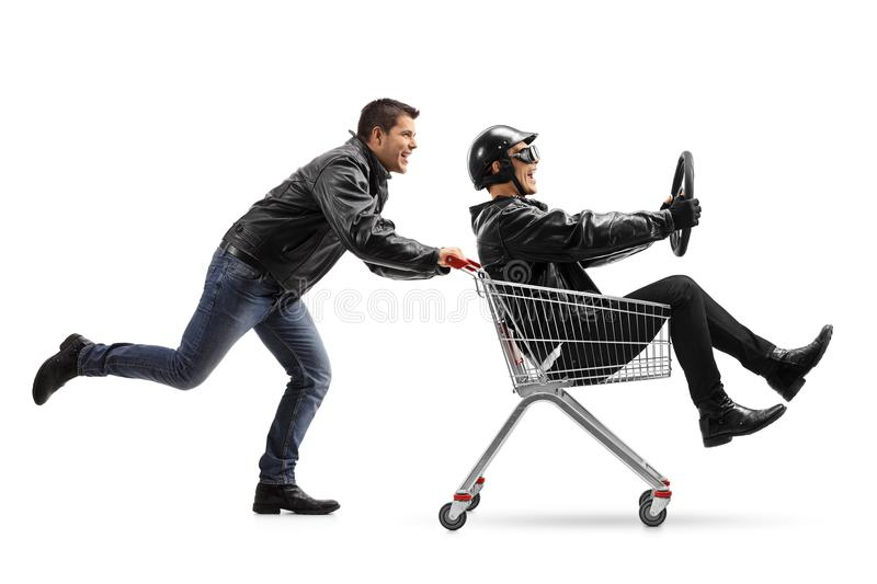 Biker pushing a shopping cart with another biker holding a steer royalty free stock photo