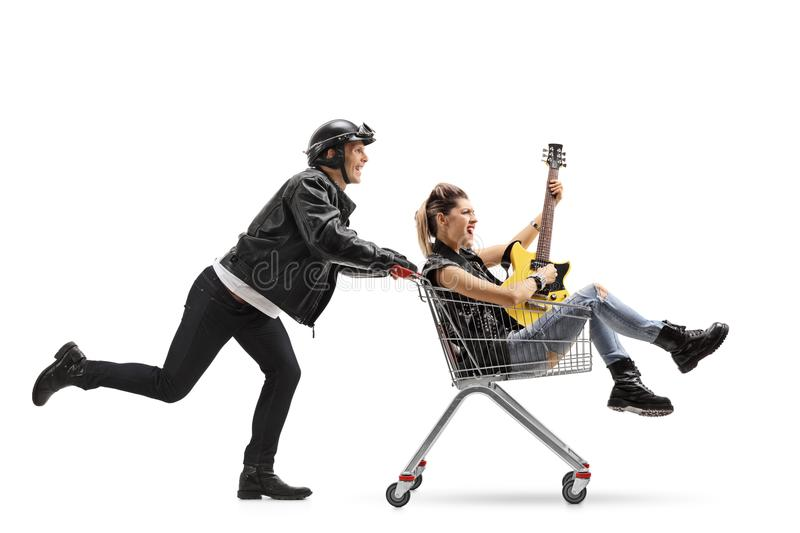 Biker pushing a shopping cart with a punk girl riding inside stock images