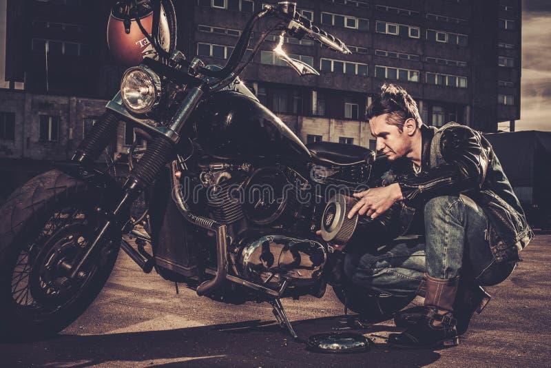 Biker repairing his custom motorcycle bobber. On a road stock image
