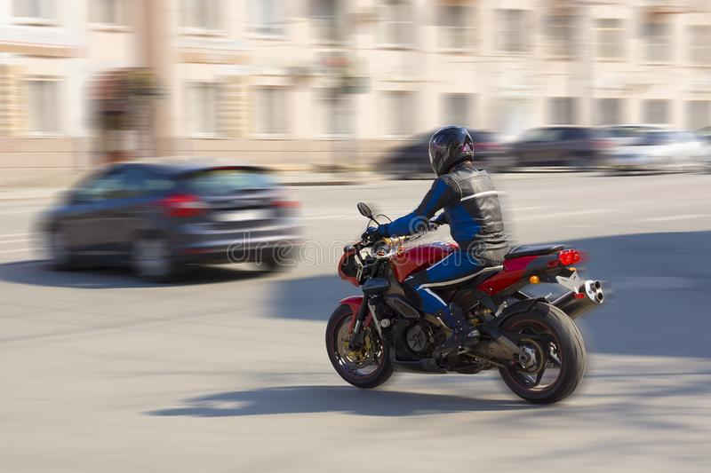 Biker rides on a city road royalty free stock photography