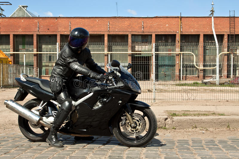 Biker riding motorcycle in old factory royalty free stock photo