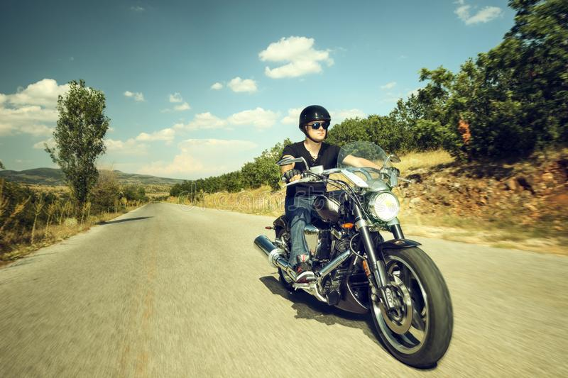 Biker riding a motorcycle royalty free stock images