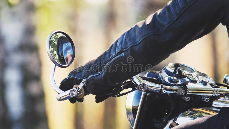 Biker`s hand on the handle of his cool bike. Outdoors stock photo