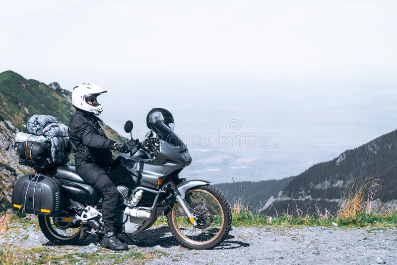 Biker is sitting on his adventure motorcycle, the top mountain in background, enduro, off road, beautiful view, danger road in royalty free stock images
