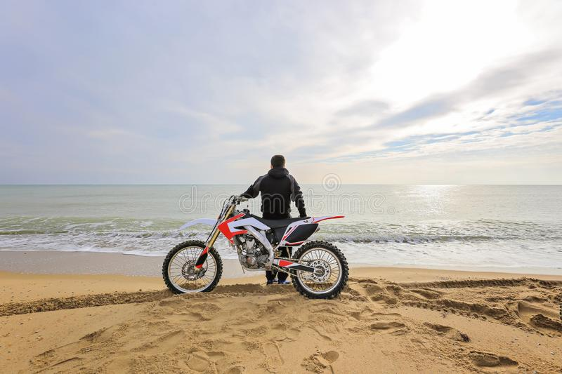Biker sitting on a motorcycle on the beach royalty free stock photos