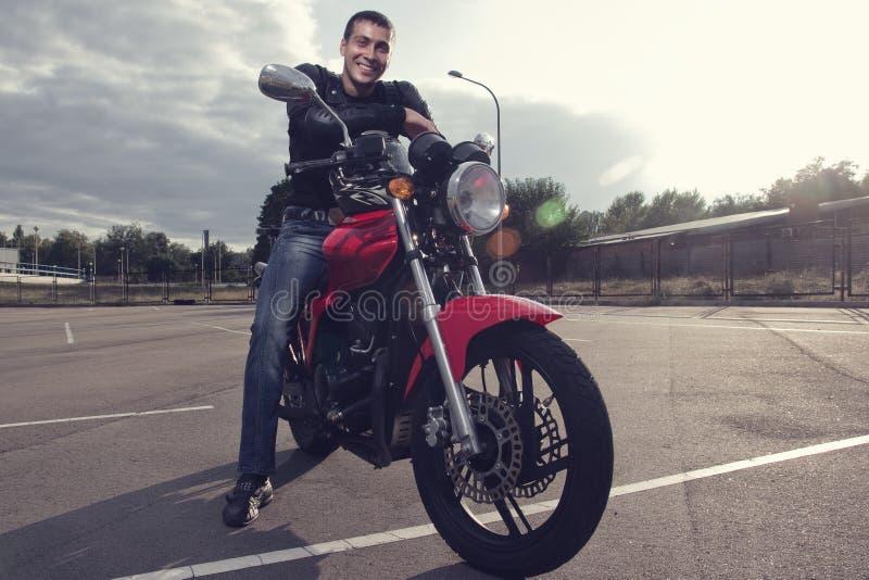 Biker sitting on sporty motorcycle stock photos