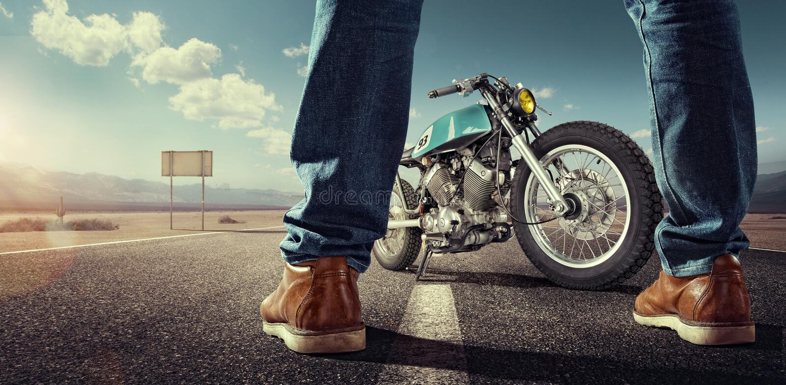 Biker standing near the motorcycle on an empty road. Sport. Biker standing near the motorcycle on an empty road at sunny day. Close view on legs stock photography