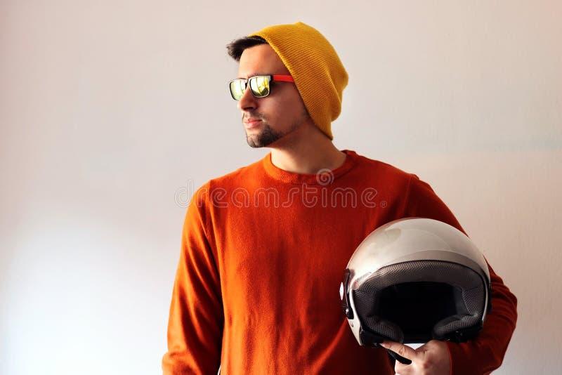 Biker vestito di arancione e con berretto giallo e occhiali da sole con il casco grigio in mano immagine stock